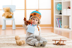 Happy child boy playing with wooden toy airplane and teddy bear on floor in nursery room Royalty Free Stock Image