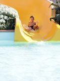 Happy child boy riding slides in aqua park Royalty Free Stock Images