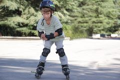 Happy child boy on roller skates outdoors Stock Image