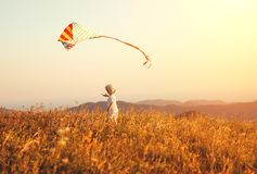 Happy child boy running with kite at sunset outdoors Royalty Free Stock Photos