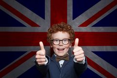 Happy child boy showing thumb up against the UK flag background. Learn English its cool.  stock photos