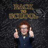 Happy child boy showing thumb up in classroom on chalkboard background. Back to school concept.  royalty free stock photography