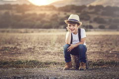 Happy child. Happy boy sitting on the field Stock Photo