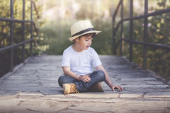 Happy child. Happy boy sitting in the field with hat Stock Photos