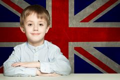 Happy child boy student in classroom against the UK flag background. Learn English concept stock image