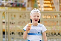 Happy child boy 5-6 years old walking in an amusement Park and eating ice cream. Children lifestyle
