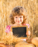 Happy child with bread in field Stock Photos