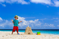 Happy child with built sand castle on the beach Stock Photo