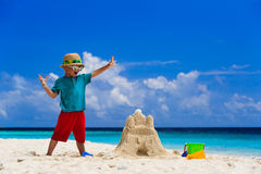Happy child with built sand castle on the beach Stock Image