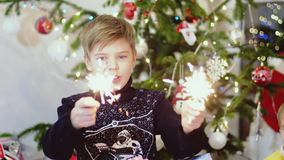 Happy child burn sparklers among bokeh lights and garlands on a Christmas tree. slow motion. 3840x2160, 4k stock footage