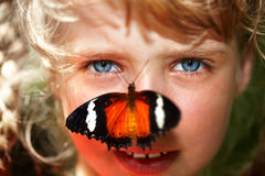 Happy child with butterfly on neck. Royalty Free Stock Photo