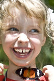 Happy child with butterfly on neck. Royalty Free Stock Images