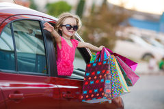 Happy child in the car with colored bags Royalty Free Stock Photography