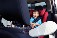Happy child in the car. Mid shot of a smiling broadly child, placing his legs on front seat. Sitting in the car in the seat for children, having fun stock images