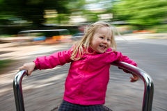 Happy child on a carousel. Little girl having fun in a carousel. Rotating very fast with a beautiful motion blur in the background royalty free stock image