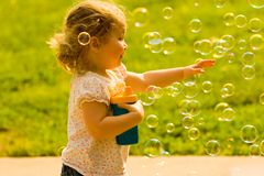 Happy Child Chasing Soap Bubbles. Young girl reaching for soap bubbles. Please look at my other bubble image with children trying to catch bubbles, if you like royalty free stock photography