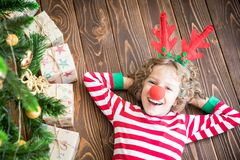 Happy child on Christmas eve. Happy child wearing reindeer Rudolph. Funny kid on Christmas eve. Xmas holiday concept Stock Photography