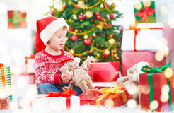 Happy child with Christmas gifts near a Christmas tree Royalty Free Stock Image