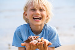 Happy child with collection of shells at beach. Happy, smiling child holding collection of shells at the beach Stock Photo