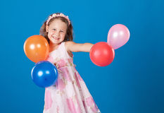 Happy child with colorful air ballons over blue Royalty Free Stock Images