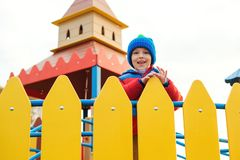 Happy child on colorful castle playground. Cute little boy playing outdoors in cold autumn time. Happy and healthy childhood. stock photo