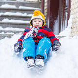 Happy child in colorful clothes having fun with riding on snow, Stock Images