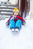 Happy child in colorful clothes having fun with riding on snow, Royalty Free Stock Photo
