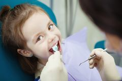 Happy child in dentist chair with napkin on chest. Happy child in comfortable dentist chair with paper napkin on chest and doctor in rubber gloves who checks Stock Photos