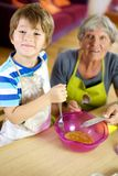 Happy child cooking with grandmother at home royalty free stock photography