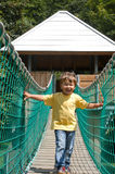 Happy child crossing over suspension bridge Royalty Free Stock Images