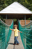 Happy child crossing over suspension bridge Royalty Free Stock Photo