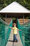 Happy child crossing over suspension bridge Royalty Free Stock Photo