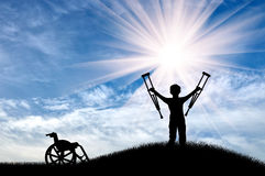 Happy child with crutches disabled person next to wheelchair on hill day. Disabled child standing with crutches alongside wheelchair on the hill day. Concept of royalty free stock photo