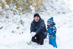 Happy child and dad having fun with snow in winter. Winter portrait of kid boy and dad in colorful clothes, outdoors during snowfall. Active outoors leisure with stock photography