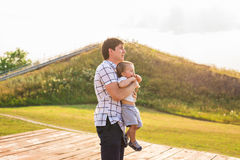 Happy child, dad and son having fun, holding on hands on a sunlight sunset background. Family, travel, vacation. Childhood, father`s day - concept Stock Photography
