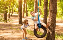 Happy child daughter pushing father on tire swing in garden