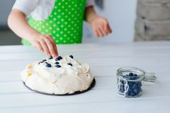 Happy child decorating meringue with blueberries Royalty Free Stock Image