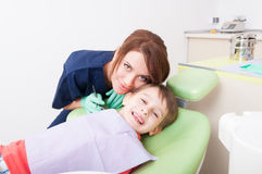 Happy child in dental office or at dentist. Friendly and careful women doctor Royalty Free Stock Image