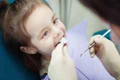 Happy child in dentist chair with napkin on chest. Happy child in comfortable dentist chair with paper napkin on chest and doctor in rubber gloves who checks stock image