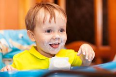 Happy child dirty with cream yoghurt Stock Images