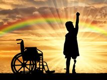 A happy child is a disabled girl with a prosthetic leg in the open air at sunset near the sea, and a wheelchair. The concept of children with prosthetic leg royalty free stock photography