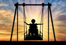 Happy child is disabled in a wheelchair on an adaptive swing for disabled children. Lifestyle of children with disabilities stock photography