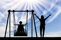 Happy child is disabled in a wheelchair on an adaptive swing for disabled children with mom. Lifestyle and support for disabled children stock photo
