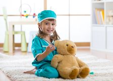 Happy child doctor girl examines teddy bear in nursery room at home. royalty free stock photo