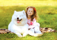 Happy child and dog having fun in sunny autumn day Stock Photography