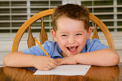 Happy child doing his homework. At kitchen table at home stock photography