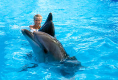 Happy child and dolphins in blue water. Dolphin Assisted Therapy. Child and dolphins in blue water. Dolphin Assisted Therapy royalty free stock photography