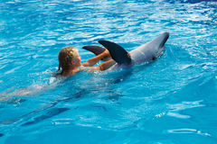 Happy child and dolphins in blue water. Dolphin Assisted Therapy. Child and dolphins in blue water. Dolphin Assisted Therapy stock image