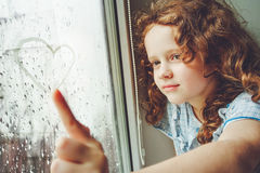 Happy child drawing heart on the window. Royalty Free Stock Images