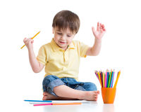 Happy child drawing with pencils in album Stock Photos